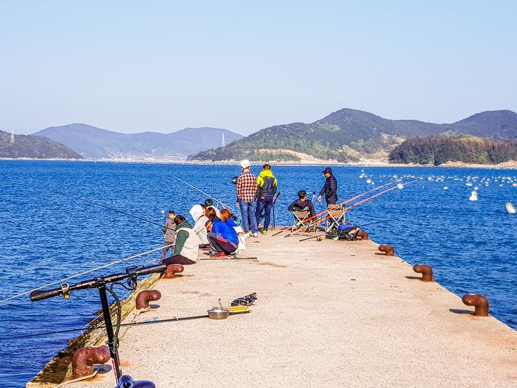 Tongyeong, Steg mit Anglern im Meer